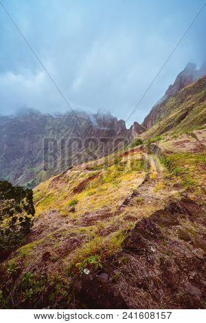 Rugged Mountain Range Overgrown With Verdant Grass And Encase By Fog . Xo-xo Valley. Santo Antao Isl