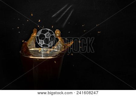 A Chalk-drawn Soccer Ball Flies In A Glass With Beer On A Black Chalkboard Background. Splashes Of B