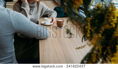 The Lovely Couple In Love Hold Hands In Restaurant. Couple Holding Hands Sitting On Chairs. There Is
