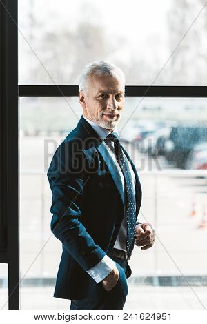 Portrait Of Handsome Senior Businessman Standing With Hand In Pocket And Smiling At Camera