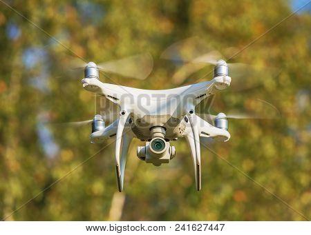 Wallisellen, Switzerland - September 23, 2017: A Dji Phantom 4 Pro Drone Flying, Trees In The Backgr