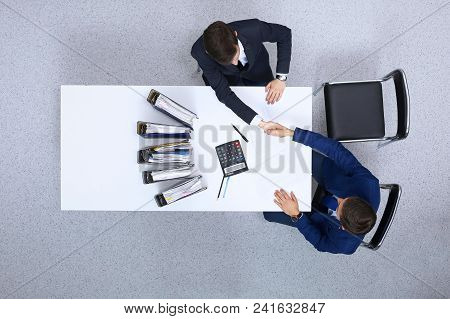 Two Businessmen Shaking Hands While  Sitting At The Table, View From Above. Bookkeeper Or Financial