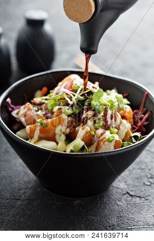 Poke bowl with salmon and vegetables, green onions and microgreens with soy souce pouring over poster