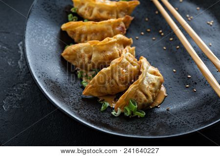 Fried Potstickers With Green Onions On Black Plate