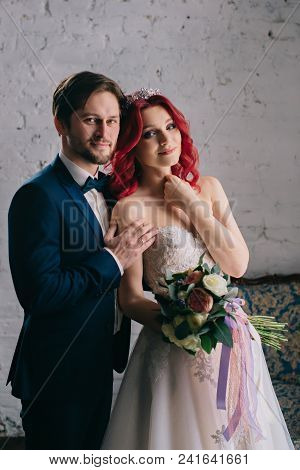 Portrait Of Happy Newlyweds Who Laugh And Cuddle In A Loft-style Room, Close-up