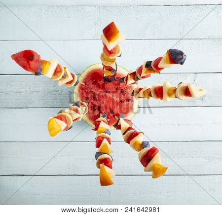 Table Top Shot Of A Colorful Mixed Seasonal Fruit Salad Served On Barbecue Sticks, Stuck In A Waterm