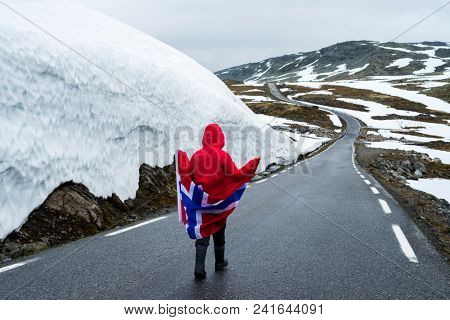 Bjorgavegen - Snowy road in Norway. Girl with the Norwegian flag on a mountain road near a wall of snow. Tourist Route Aurlandsfjellet runs from Aurlandsvangen to Laerdalsoyri
