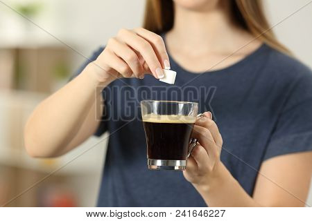 Front View Close Up Of A Woman Hands Throwing A Sugar Cube Into A Coffee Cup At Home