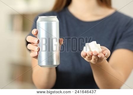 Front View Close Up Of A Woman Hands Holding A Soda Drink Can And Sugar Cubes At Home