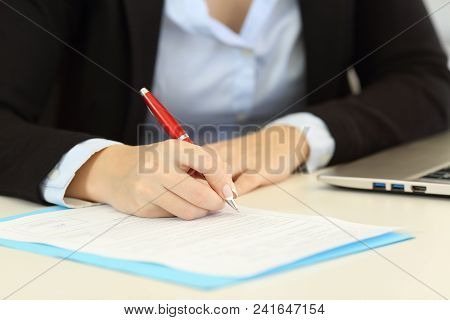Front View Close Up Portrait Of An Executive Hands Filling A Form On A Desktop