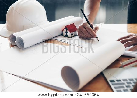 Creative Architect Projecting On The Big Drawings In The Dark Loft Office Or Cafe With Dark And Retr