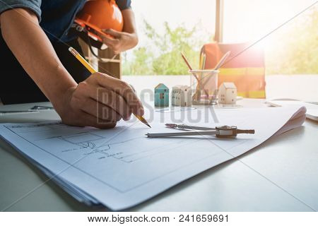 Hands Of Architect Or Engineer With Helmet Using Pencil Working With Blueprint On Desk In Office . E