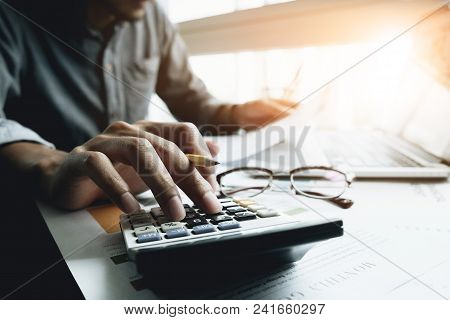 Close Up Of Businessman Or Accountant Hand Holding Pencil Working On Calculator To Calculate Financi