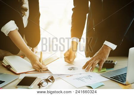 Business Team Analyzing Financial Document And Calculator On Workplace - Corporate Organization Meet