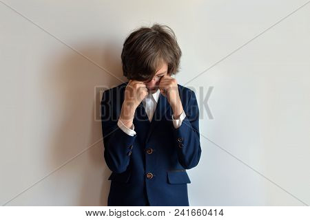 The Schoolboy Is In Despair. The Schoolboy Is Crying. Schoolboy In Uniform With Closed Face On A Whi