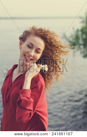 Girl With Curly Hair. She Fervently Laughs And Holds White Flower In Her Hands. Spring Time. Close-u