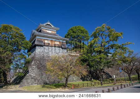 wooden turret or yagura on stone wall of Kumamoto castle in Japan and green tree with clear blue sky and copy space poster