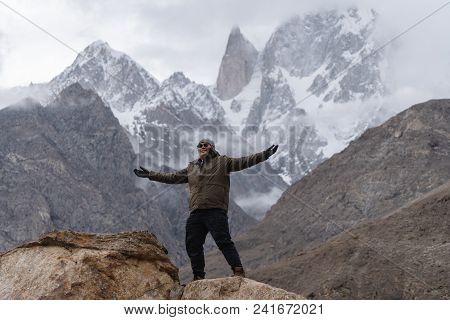 A Man Raising Hand Up On The Mountain Peak And Ladyfinger Mountain Peak Background, In Pakistan