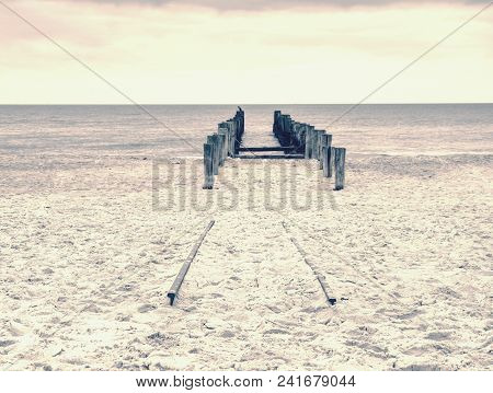 Seascape Within Misty  Sunrise , Silky Sea With Wooden Poles Against A Pastel Sky. Wooden Poles Of A