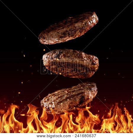Flying beef minced hamburger pieces above grill flames, isolated on black background. Concept of flying food, very high resolution image