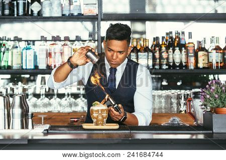 Mixed Race Male Expert Bartender Is Using Cinnamon Powder And A Blowtorch For Decorating A Cocktail
