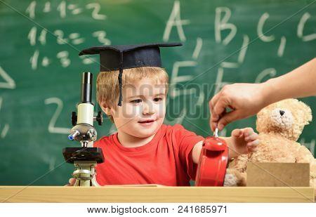 School Break Concept. Child On Smiling Face Looks At Alarm Clock. Pupil Waiting For School Break. Ki
