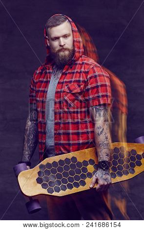 Bearded Man With Tattooes On His Arms Holding Longboard.