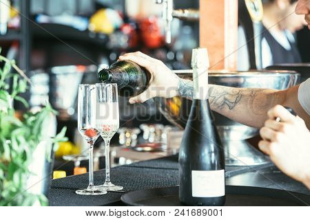 Close Up Of A Cropped View Of The Hands Of A Tattooed Waiter Is Serving Alcohol In A Glass Ready To