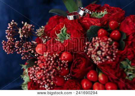 Classic White Gold Wedding Rings On Red Bouquet, Horizontal Shot.