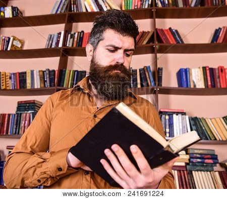 Man On Busy Thoughtful Face Reading Book, Bookshelves On Background. Teacher Or Student With Beard S