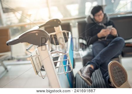 Young Asian Man Using Smartphone And Listening To Music While Waiting For Connecting Flight On Bench