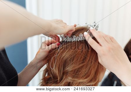 Hairdresser Makes Models Hairstyle For Bride, Putting On Tiara Crown. Close-up Shot With No Face.