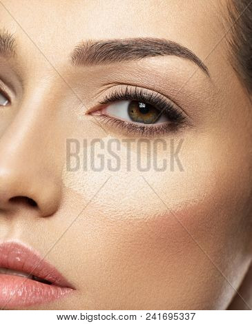 Cosmetic makeup tonal foundation is on woman's face. Skin care concept.