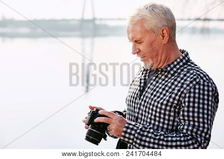 Unwritten Story. Meditative Mature Man Holding Camera And Looking Down