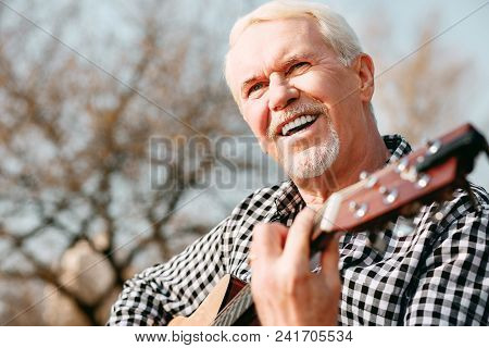 Mental Health. Low Angle Of Merry Mature Man Laughing And Enjoying Guitar Play