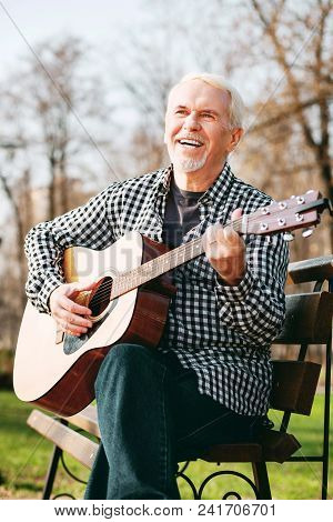 Guitar Sound. Low Angle Of Merry Mature Man Laughing And Playing Guitar