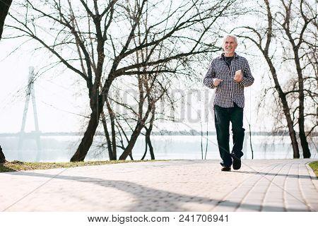 Excellent Walk. Positive Senior Man Strolling And Enjoying Nature