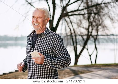 Nature And Music. Cheerful Senior Man Strolling And Enjoying Music