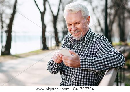 Best Playlist. Jovial Senior Man Wearing Earphones And Listening To Music