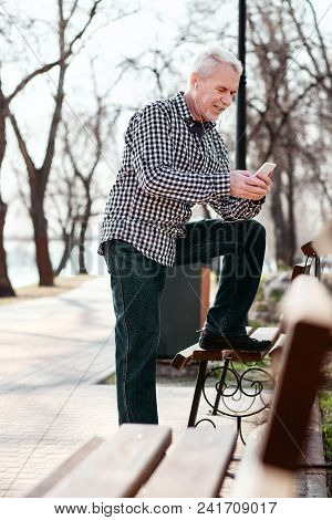 Online Playlist. Low Angle Of Musing Senior Man Using Phone And Listening To Music