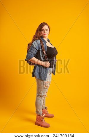 Confident curvy girl in denim jacket with backpack looking at ca poster