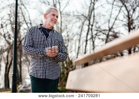 Music For Everyone. Low Angle Of Doubtful Senior Man Standing In Park And Listening To Music