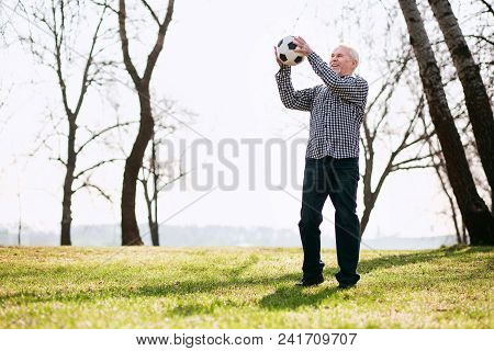 Fun With Ball. Positive Mature Man Exercising With Ball And Standing On Grass
