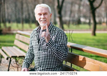 Its Dangerous. Appealing Senior Man Posing On Bench And Rising Finger