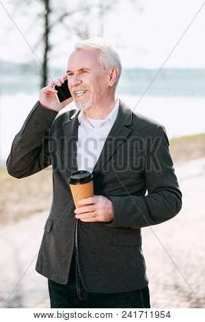 Coffee In Park. Optimistic Senior Businessman Drinking Coffee In Park And Talking On Phone