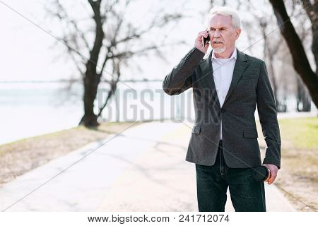 Business Issue. Frowned Senior Businessman Standing In Park And Talking On Phone