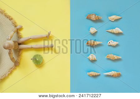 Wooden doll with fresh citric drink on yellow as sand beach and blue as water. Concept tan and beach. Summer. View from above. Danger of sunburn. Uv protective. Dreams will learn to swim. poster