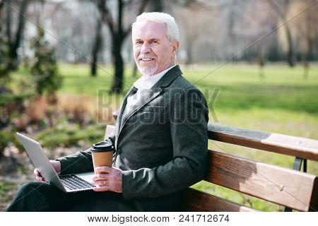 Warm Weather. Enthusiastic Mature Businessman Using Laptop While Drinking Coffee