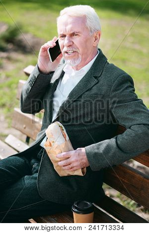 No Rest. Top View Of Experienced Mature Businessman Talking On Phone And Consuming Sandwich
