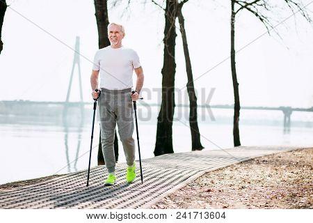Great Sport. Vigorous Mature Man Practicing Race Walking In Park While Enjoying Nature